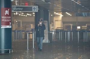 An officer wears a mask as he walks in Terminal 3 at Rome's Fiumicino international airport after a fire broke out overnight on May 7, 2015. in its main terminal for international flights. No serious injuries were reported as a result of a blaze which took hold around 5:00 am (0300 GMT) in terminal three of the Italian capital's main hub, which is located on the coast around 30km (20 miles) west of the city. Several airport employees were suffering from the effects of smoke inhalation, airport officials said.  AFP PHOTO / TIZIANA FABI        (Photo credit should read TIZIANA FABI/AFP/Getty Images)