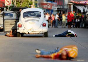 The bodies of three dead people lie on a street in downtown Acapulco, Guerrero State, Mexico, on August 29, 2014. Guerrero is one of Mexico's poorest and most violent states, where a lucrative drug trade has flourished. Drug trafficking in the state is dominated by the Los Rojos criminal gang, based in the regional capital Acapulco.  AFP PHOTO/ Pedro PARDO        (Photo credit should read Pedro PARDO/AFP/Getty Images)