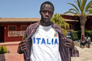 """A migrant poses with a tee-shirt reading """"Italia"""" after his arrival at the Palazzolo Acreide immigration center, on April 17, 2015 in Sicily. The U.N. refugee agency said over 35,000 refugees and migrants have crossed the Mediterranean Sea (including 23,500 who landed in Italy and over 12,000 in Greece) in 2015. At the same time, some 950 people have been reported dead or missing at sea. Last year some 219,000 refugees and migrants crossed the Mediterranean (Italy alone received over 170,000). Most of them were rescued by the Italian Navy, the Coast Guard or merchant vessels. It is estimated that some 3,500 people lost their lives at sea last year.  AFP PHOTO / GIOVANNI ISOLINO        (Photo credit should read GIOVANNI ISOLINO/AFP/Getty Images)"""