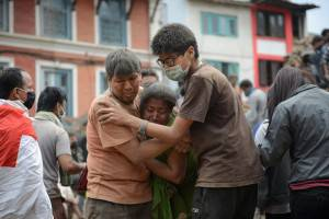 Earthquake victims are helped by a rescuer in Kathmandu's Durbar Square, a UNESCO World Heritage Site that was severely damaged by the earthquake on April 25, 2015. A massive 7.8 magnitude earthquake killed hundreds of people April 25 as it ripped through large parts of Nepal, toppling office blocks and towers in Kathmandu and triggering a deadly avalanche that hit Everest base camp. AFP PHOTO / PRAKASH MATHEMA        (Photo credit should read PRAKASH MATHEMA/AFP/Getty Images)
