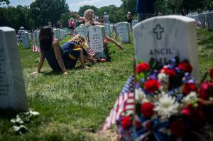 ARLINGTON, VA - MAY 25:   Angela Spraul, with her daughters Alana, 6,  sitting, and Ava, 4, visit the grave of her husband John Spraul, U.S. Navy, who died Feb. 28, 2013, at Section 60 on Memorial Day at Arlington National Cemetery on May 25, 2015 in Arlington, Va. U.S. President Barack Obama, Chairman of the Joint Chiefs of Staff U.S. Army General Martin Dempsey and U.S. Defense Secretary Ash Carter honored fallen soldiers during a ceremony at Arlington on this Memorial Day.  (Photo by Gabriella Demczuk/Getty Images)