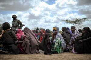 """A handout photograph taken on August 4, 2013 and released by the African Union-United Nations Information Support Team A shows internally displaced women waiting at a food distribution center in Afgoye, Somalia. The United Arab Emirates (UAE) Red Crescent gave out food aid as part of a program they are conducting during the month of Ramadan. Over 5,000 internally displaced persons were given food during the NGO's trip to Afgoye, which was aided in part by AMISOM forces. AFP PHOTO / AU-UN IST PHOTO / TOBIN JONES RESTRICTED TO EDITORIAL USE - MANDATORY CREDIT """"AFP PHOTO / AU-UN IST PHOTO / TOBIN JONES"""" - NO MARKETING NO ADVERTISING CAMPAIGNS - DISTRIBUTED AS A SERVICE TO CLIENTS        (Photo credit should read TOBIN JONES/AFP/Getty Images)"""