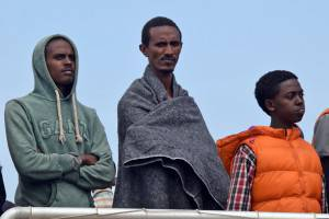 Migrants wait to disembark from Migrant Offshore Aid Station (MOAS) ship in the port of Messina, on May 16, 2015 following rescue operations at sea off the coast of Sicily in partnership with NGO Doctors Without Borders (MSF). AFP PHOTO / GIOVANNI ISOLINO        (Photo credit should read GIOVANNI ISOLINO/AFP/Getty Images)