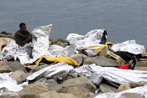 A migrant protecting himself with an emergency blanket wakes up on the rocks off the coast of Ventimiglia, Italy, on June 14, 2015 after having spent the night near the sea at the French-Italian border, after being refused entry into France. Italian police moved on June 13 to disperse around 200 migrants who were staging a sit-in at a border crossing with France after French police refused to let them enter the country. However, a group of around 50 men slipped away from the police cordon and took refuge on rocks near the border post. AFP PHOTO / JEAN-CHRISTOPHE MAGNENET        (Photo credit should read JEAN-CHRISTOPHE MAGNENET/AFP/Getty Images)