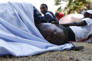 A migrant sleeps on the border near the sea in the Italian city of Ventimiglia at the Italian-French border on June 21, 2015, where a group of migrants has been camping since being refused entry into France. Italy warned that EU solidarity is at stake if the 28-nation bloc fails to reach a deal on sharing the burden of the Mediterranean migrant crisis. AFP PHOTO / VALERY HACHE        (Photo credit should read VALERY HACHE/AFP/Getty Images)