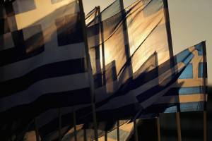 """ATHENS, GREECE - JULY 05: The sun sets through Grrek flags over the Greek parliament as the polls have now closed in the Greek austerity referendum and people are begining to gather in the squares of Athens waiting for the official result on July 5, 2015 in Athens, Greece. The people of Greece are going to the polls to decide if the country should accept the terms and conditions of a bailout with its creditors. Greek Prime Minister Alexis Tsipras is urging people to vote """"a proud no"""" to European creditors' proposals, and """"live with dignity in Europe"""". 'Yes' campaigners believe that a no vote would mean financial ruin for Greece and the loss of the Euro currency.  (Photo by Christopher Furlong/Getty Images)"""