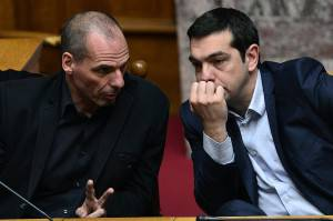 Greek Prime Minister Alexis Tsipras (R) listens to his Finance Minister Yianis Varoufakis during the vote for the president, at the Greek parliament in Athens, on February 18, 2015.  Greece's parliament elected pro-European conservative Prokopis Pavlopoulos as the country's new president, a move calculated to bolster the hard-left government in its critical EU bailout talks. AFP PHOTO / LOUISA GOULIAMAKI        (Photo credit should read LOUISA GOULIAMAKI/AFP/Getty Images)