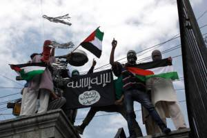 SRINAGAR, INDIA - JULY 18: Kashmiri protesters hold up a flag of the Islamic State of Iraq and the Levant (ISIL), during a protest against Israeli military operations in Gaza, on July 18, 2014 in Srinagar, India. The death toll in Gaza hit 265 as Israel pressed a ground offensive on the 11th day of an assault aimed at stamping out rocket fire, medics said. (photo by Waseem Andrabi/Hindustan Times via Getty Images)