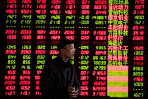 An investor looks at stock informations at a trading hall of a securities firm in Shanghai on January 28, 2014. Chinese shares ended lower on worries over market liquidity, dealers said.  AFP PHOTO / JOHANNES EISELE        (Photo credit should read JOHANNES EISELE/AFP/Getty Images)