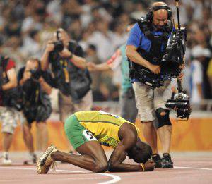 "Photographers and a cameraman film Jamaica's Usain Bolt as he celebrates winning the men's 200m final at the ""Bird's Nest"" National Stadium during the 2008 Beijing Olympic Games on August 20, 2008. Bolt became the first man in 24 years to claim the Olympic sprint double when he won the 200m in a new world record time of 19.30sec. Netherlands Antilles' Churandy Martina claimed silver in 19.82sec and Shawn Crawford of the US took bronze in 19.96sec.  AFP PHOTO / OLIVIER MORIN (Photo credit should read OLIVIER MORIN/AFP/Getty Images)"
