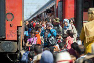 Migrants stand on a platform at the train station in the town of Gevgelija, on the Macedonian-Greek border, as they try to board trains to Serbia on August 23, 2015. More than 1,500 mostly Syrian refugees, trapped in a no-man's land for three days, entered Macedonia from Greece, after police allowed them to pass despite earlier trying to hold back the crowd using stun grenades. AFP PHOTO / ROBERT ATANASOVSKI        (Photo credit should read ROBERT ATANASOVSKI/AFP/Getty Images)