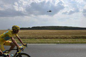Italy's Vincenzo Nibali, wearing the overall leader's yellow jersey, rides in the pack as a media helicopter flies behind during the 137.5 km twenty-first and last stage of the 101st edition of the Tour de France cycling race on July 27, 2014 between Evry and Paris.  AFP PHOTO / JEFF PACHOUD        (Photo credit should read JEFF PACHOUD/AFP/Getty Images)
