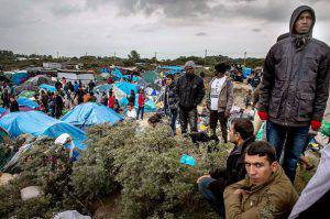 "People stand at a site dubbed the ""New Jungle"", where some 3,000 people have set up camp -- most seeking desperately to get to England, in Calais on September 21, 2015. The slum-like migrant camp sprung up after the closure of notorious Red Cross camp Sangatte in 2002, which had become overcrowded and prone to violent riots. However migrants and refugees have kept coming and the ""New Jungle"" has swelled along with the numbers of those making often deadly attempts to smuggle themselves across the Channel. AFP PHOTO / PHILIPPE HUGUEN (Photo credit should read PHILIPPE HUGUEN/AFP/Getty Images)"