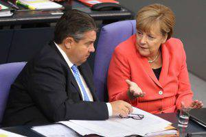 BERLIN, GERMANY - SEPTEMBER 24:  German Chancellor Angela Merkel (CDU, R) speaks to Vice Chancellor and Economy and Energy Minister Sigmar Gabriel (SPD) in the Bundestag, the German federal Parliament, on September 24, 2015 in Berlin, Germany. The European Union, after deciding upon a controversial quota system to divide the recent influx of migrants throughout Europe, will give an additional one billion euros (1.1 billion USD) to United Nations agencies dealing with the refugee crisis, according to a draft statement by officials who met in Brussels the previous day.  (Photo by Adam Berry/Getty Images)