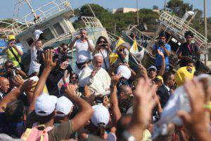 """Pope Francis passes by remains of migrants boats as he waves upon arrival during his visit to the island of Lampedusa, a key destination of tens of thousands of would-be immigrants from Africa, on July 8, 2013. Pope Francis called for an end to """"indifference"""" to the plight of refugees on Monday on a visit to an Italian island where tens of thousands of migrants from Africa and the Middle East first reach Europe.    AFP PHOTO / MARCELLO PATERNOSTRO        (Photo credit should read MARCELLO PATERNOSTRO/AFP/Getty Images)"""