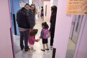 Parents arrive with their children at the Merlin preschool in Paris, on September 1, 2015, for the start of the new school year. AFP PHOTO / LIONEL BONAVENTURE (Photo credit should read LIONEL BONAVENTURE/AFP/Getty Images)