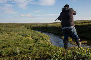 NEWTOK, AK - JULY 02: Eddie Lopez hunts for duck on Nelson Island on July 2, 2015 near Newtok, Alaska. Newtok has a population of approximately of 375 ethnically Yupik people and was established along the shores of the Ninglick River, near where the river empties into the Bering Sea, by the Bureau of Indian Affairs (BIA) in 1959. The Yupik people have lived on the coastal lands along the Bering Sea for thousands of years. As global temperatures rise the village is being threatened by the melting of permafrost, greater ice and snow melt and larger storms from the Bering Sea. According to the U.S. Army Corp of Engineers, the highest elevated point in Newtok - the school - could be underwater by 2017. Approximately nine miles away, Mertarvik has been established, though families have been slow to relocate to the new village. (Photo by Andrew Burton/Getty Images)
