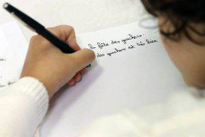 A left-handed child writes in the Salle du Pont du Buy in Brive-la Gaillarde, where writing and cooking workshops were organised and objets for the left-handed were sold, at the occasion of the French National Lefties' Day on August 23, 2015. AFP PHOTO / DIARMID COURREGES (Photo credit should read DIARMID COURREGES/AFP/Getty Images)