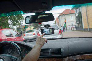 DARMSTADT, GERMANY - AUGUST 23: (EDITOR'S NOTE: The license plate has been pixelated) In this photo illustration a smartphone with the video app hangs attached inside the windshield of a car on August 23, 2014 in Darmstadt, Germany. A German court recently confirmed a ban on the use of dashcams, claiming a continuous filming by drivers is an infringement on other people's right to privacy. (Photo by Thomas Lohnes/Getty Images)