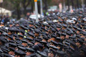 NEW YORK, NY - OCTOBER 28: Thousands of police officers from around the country stand in the rain for the funeral of slain NYPD Officer Randolph Holder at Greater Allen A.M.E. Cathedral of New York on October 28, 2015 in the Queens borough of New York City. Holder, 33, was gunned down while chasing a suspect in East Harlem last week, the fourth officer to be fatally shot in the line of duty in New York City in the last 10 months. Tyrone Howard was taken into custody a few blocks away and has been charged with murder and robbery. Holder will be buried in Guyana. (Photo by Spencer Platt/Getty Images)