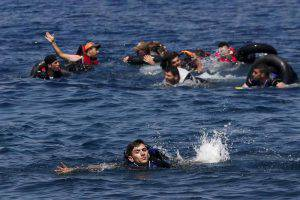 Syrian and Afghan refugees swim towards the sea after their dinghy deflated some 100m away before reaching the Greek island of Lesbos, September 13, 2015. REUTERS/Alkis Konstantinidis