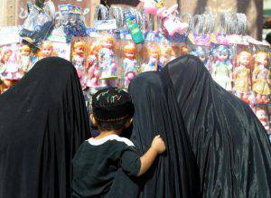 """Three Iraqi Muslim women and a child look at dolls 08 September 2003 at a bazaar in Najaf. In his first major speech on Iraq since May, US President George W. Bush urged the United Nations to overcome """"past differences"""" over the US-led invasion of Iraq, appealing even to opponents of the war for troops and money. AFP PHOTO/Karim SAHIB (Photo credit should read KARIM SAHIB/AFP/Getty Images)"""