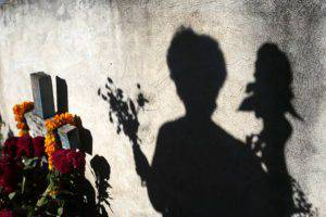 The shadow of a woman adorning a tomb with flowers casts on a wall at the cemetery in Tixtla, Guerrero State, Mexico, during the celebration of All Souls Day on November 2, 2015. AFP PHOTO / Pedro PARDO (Photo credit should read Pedro PARDO/AFP/Getty Images)