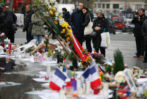 "People gather in front of a makeshift memorial in Place de la Republique square in Paris, on November 27, 2015, for the National Tribute to the 130 people killed in the November 13 Paris attacks. Families of those killed in France's worst-ever terror attack, claimed by the Islamic State (IS) group, will join some of the wounded at ceremonies at the Invalides, the gilded 17th-century complex in central Paris that houses a military hospital and museum and Napoleon's tomb. The tribute will be ""National and Republican,"" an official at the Elysee presidential palace said, referring to the French republic's creed of liberty, equality and fraternity. AFP PHOTO / THOMAS SAMSON / AFP / THOMAS SAMSON (Photo credit should read THOMAS SAMSON/AFP/Getty Images)"