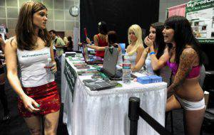 Webcam girls with laptops stay online at their booth on opening day of the 2011 Exxxotica Expo on August 26, 2011 in Los Angeles, California. Exxxotica is one of the country's leading adult consumer events, featuring a diverse array of exhibitors showcasing the latest products appealing to like-minded adults, with seminars, stage shows and stars signing autographs for fans of the adult entertainment industry. AFP PHOTO/Frederic J. BROWN (Photo credit should read FREDERIC J. BROWN/AFP/Getty Images)