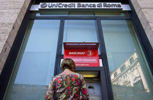 (FILES) - A customer makes an operation at an ATM of the Unicredit Bank branch in Rome on September 20, 2011. Italy's top bank UniCredit announced on November 11, 2015 it would cut its staff by 18,200 positions by 2018 to save 1.6 billion euros ($1.71 billion).  AFP PHOTO / ANDREAS SOLARO        (Photo credit should read ANDREAS SOLARO/AFP/Getty Images)