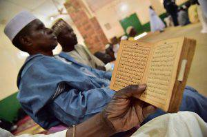 """A man reads the Quran in the Bangui's Mosque before the arrival of the Pope Francis for a visit on November 30, 2015 as part of his papal trip to Africa. Pope Francis arrived as """"a pilgrim of peace"""" in conflict-ridden Central African Republic on November 29, flying in from Uganda on what will be the most dangerous destination of his three-nation Africa tour. AFP PHOTO / GIUSEPPE CACACE / AFP / GIUSEPPE CACACE (Photo credit should read GIUSEPPE CACACE/AFP/Getty Images)"""