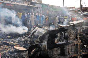 People gather to look at a burnt vehicle  following a bomb explosion that rocked the busiest roundabout near the crowded Monday Market in Maiduguri, Borno State, on July 1, 2014. A truck exploded in a huge fireball killing at least 15 people on July 1 in the northeast Nigerian city of Maiduguri, the latest attack in a city repeatedly hit by Boko Haram Islamists.  AFP PHOTO/STRINGER        (Photo credit should read STRINGER/AFP/Getty Images)