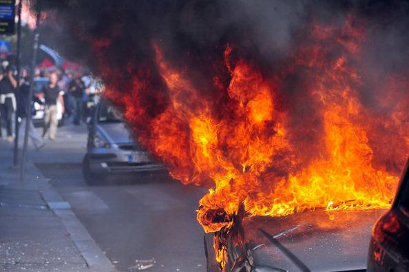 """A parked car burns during a demonstration, in dowtown Rome on October 15, 2011. Tens of thousands marched in Rome today as part of a global day of protests inspired by the """"Occupy Wall Street"""" and """"Indignant"""" movements, with the Italian capital under a security lockdown. Protesters launched worldwide street demonstrations on October 15 against corporate greed and biting cutbacks in a rolling action targetting 951 cities in 82 countries. AFP PHOTO/ ALBERTO PIZZOLI (Photo credit should read ALBERTO PIZZOLI/AFP/Getty Images)"""