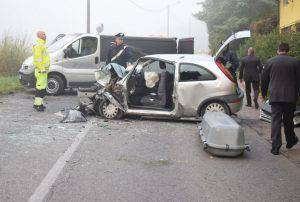 Un soccorritore osserva l'Opel Corsa distrutta (Websource)