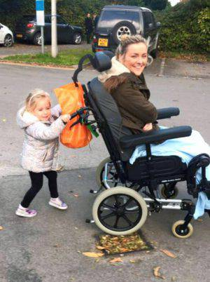 PIC FROM Caters News - (PICTURED: Helens niece Cadie-Jayne pushes Helen in her wheelchair.) - A stunning woman who woke up with neck ache was left PARALYSED just hours later. Helen Fincham, from Bridgend, Wales, woke up on August 24 with a sore neck and first thought shed slept in a funny position but by midday she could no longer feel her legs. The 21-year-old thought she was having a heart attack when her arm went numb and she became short of breath. But when paramedics arrived and asked Helen to stand she collapsed leaving everyone baffled  and she has been paralysed from the neck down ever since. After two months of tests Helen was eventually diagnosed with Transverse Myelitis  an extremely rare neurological condition whereby the spinal cord becomes inflamed and damages nerve fibres. Helen is now undergoing physio daily and despite not knowing what the future holds she remains positive and is determined to walk again. SEE CATERS COPY.