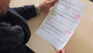 La signora mostra la cartella che le è stata recapitata (Websource)
