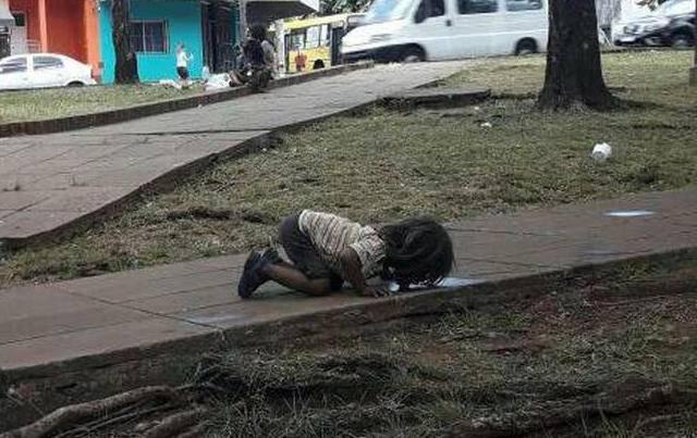 Bimba beve dalla pozzanghera: immagine simbolo della miseria