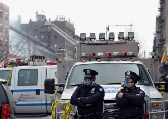 La polizia di New York, ad Harlem, Manhattan, dopo l'esplosione che ha fatto crollare due edifici il 12 marzo 2014 (STAN HONDA/AFP/Getty Images)